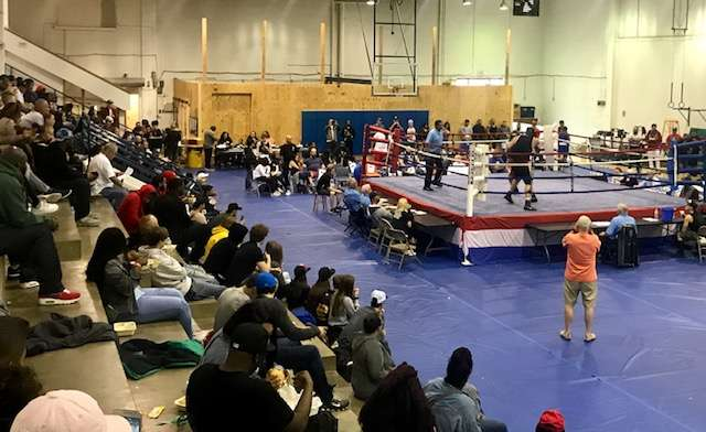 A crowd cheers on the boxers in the ring at KC PAL